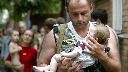 A Russian police officer carries a released baby from the school seized by heavily armed masked men and women in the town of Beslan in the province of North Ossetia near Chechnya, September 2, 2004.(Reuters / Viktor Korotayev)
