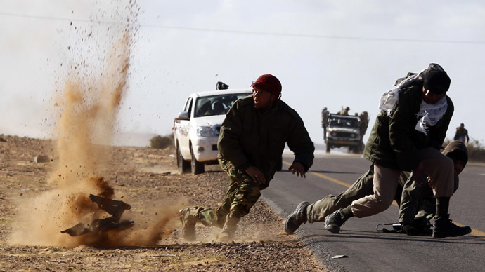 Rebel fighters jump away from shrapnel during heavy shelling by forces loyal to Libyan leader Muammar Gaddafi near Bin Jawad, March 6, 2011. (Reuters/Goran Tomasevic)