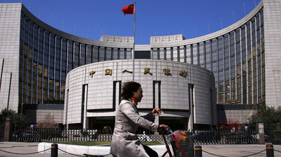 A woman rides past the headquarters of the People's Bank of China, the Chinese central bank, in Beijing (Reuters/Petar Kujundzic)