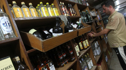 An Iraqi liquor store owner arranges imported bottles of various types of alcohol on his shop's shelves in Baghdad (AFP Photo)