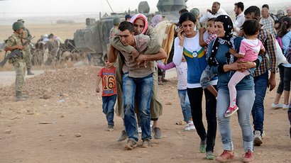 Syrian Kurds walk after crossing into Turkey at the Turkish-Syrian border, near the southeastern town of Suruc in Sanliurfa province, September 20, 2014 (Reuters / Stringer)