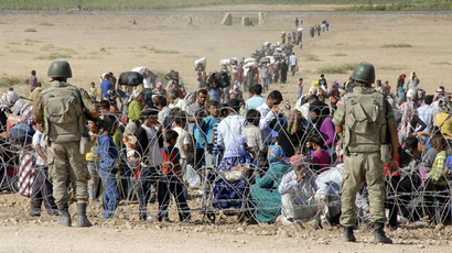 Turkish soldiers stand guard as Syrian Kurds wait behind the border fence to cross into Turkey near the southeastern town of Suruc in Sanliurfa province, September 19, 2014. (Reuters/Stringer)