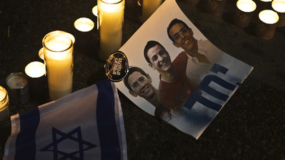 Candles placed next to a picture of three Israeli teenagers who were abducted and killed, in Tel Aviv's Rabin Square June 30, 2014. (Reuters/Nir Elias)
