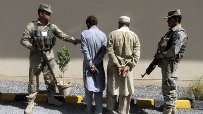 Afghan policemen detain suspected Taliban members at the site of where militants carried out an attack on NATO supply trucks in the Torkham area near the Pakistani-Afghan border last night in Jalalabad Province, September 16, 2014. (Reuters/Parwiz)