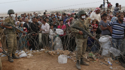 Turkish soldiers stand guard as Syrian Kurdish refugees wait behind the border fences to cross into Turkey near the southeastern town of Suruc in Sanliurfa province September 27, 2014. (Reuters/Murad Sezer)