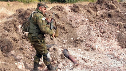 "Donetsk People's Republic militiaman are at the site of the graves of peaceful residents discovered near Mine 22 ""Kommunar"" outside Donetsk.(RIA Novosti)"