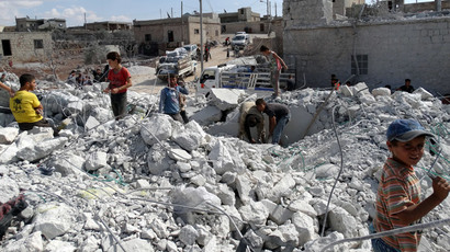 Syrians check a damaged house, reportedly hit by US-led coalition air strikes, in the village of Kfar Derian in the western Aleppo province on September 23, 2014.(AFP Photo / Sami Ali)