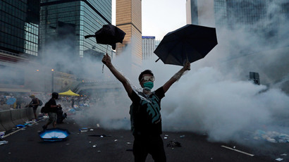 A protester (C) raises his umbrellas in front of tear gas which was fired by riot police to disperse protesters blocking the main street to the financial Central district outside the government headquarters in Hong Kong, September 28, 2014.(Reuters / Tyrone Siu)