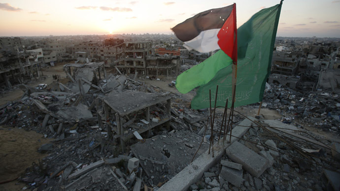A Palestinian flag and a Hamas flag (R) flutter atop the wreckage of a house, which witnesses said was destroyed during the seven-week Israeli offensive, in the east of Gaza City September 3, 2014. (Reuters/Suhaib Salem)