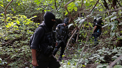 Police officers stand guard in an area where a mass grave was found, in Colonia las Parotas on the outskirts of Iguala, in Guerrero October 4, 2014 (Reuters / Jorge Dan Lopez)