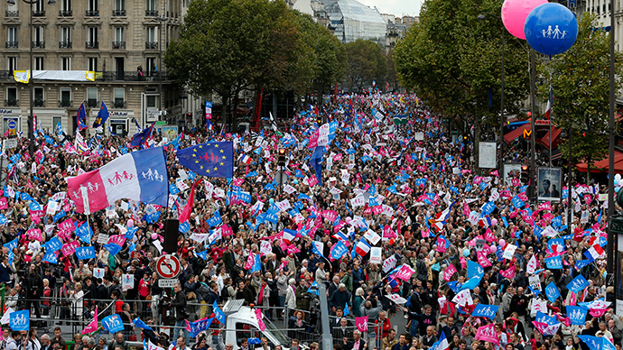 "People wave flags and hold signs with messages as tens of thousands of demonstrators take part in the ""Manif Pour Tous"" (Demonstration For All) to protest against PMA (Procreation Medicalement Assistee or Medically Assisted Reproduction) and GPA (Grosesse pour Autrui or Gestation for Others) during a march in Paris October 5, 2014 (Reuters / Gonzalo Fuentes)"