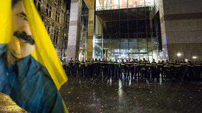 Police forces stand guard in front of the main entrance to Parliament building in The Hague, to prevent Kurdish demonstrators, waving a flag with a portrait of jailed leader of Turkey's outlawed Kurdistan Workers Party (PKK), Abdullah Ocalan, to access the building, on October 6, 2014.(AFP Photo / Valerie Kuypers )