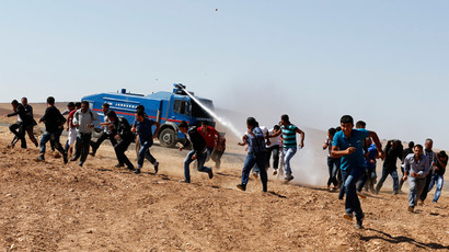 Protesters run away as an armoured army vehicle sprays water to disperse them during a pro-Kurdish demonstration in solidarity with people of Kobani, near the Mursitpinar border crossing on the Turkish-Syrian border, in the Turkish town of Suruc in southeastern Sanliurfa province October 7, 2014. (Reuters / Umit Bektas)