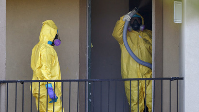 Workers in a hazardous material suits clean the apartment unit where a man diagnosed with the Ebola virus was staying in Dallas, Texas, October 6, 2014. (Reuters/Jim Young)