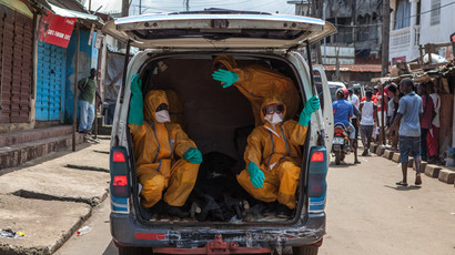Volunteers pick up bodies of the dead of the Ebola virus on October 8, 2014 in Freetown, Sierra Leone. (AFP Photo / Florian Plaucheur)