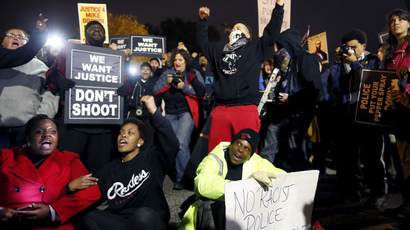Protesters sit in the middle of the street across from the police station in Ferguson, Missouri October 10, 2014. (Reuters / Jim Young)