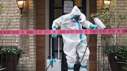 A member of the CG Environmental HazMat team disinfects the entrance to the residence of a health worker at the Texas Health Presbyterian Hospital who has contracted Ebola in Dallas, Texas, October 12, 2014. (Reuters/Jaime R. Carrero)