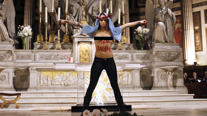 A member of Ukrainian feminist group Femen stands at the altar of the Madeleine church in Paris. (AFP Photo / Thomas Samson)
