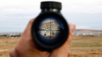A general view of the Syrian town of Kobani is seen through a spy-glass from near the Mursitpinar border crossing, on the Turkish-Syrian border in the southeastern town of Suruc, October 19, 2014. (Reuters / Kai Pfaffenbach)