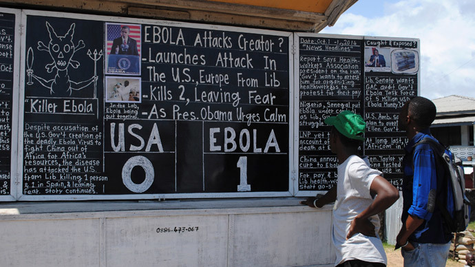 "Bystanders read headlines saying ""Ebola 1: USA 0"" at the Daily Talk, a street side chalkboard newspaper, in Monrovia (Reuters / James Giahyue)"
