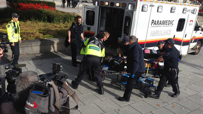 This October 22, 2014 photo shows police and medical personnel moving a wounded person into an ambulance at the scene of a shooting at the National War Memorial in Ottawa, Canada. (AFP Photo/Michel Comte)