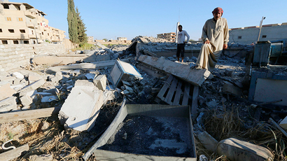 The owner of a plastics factory that was targeted on Sunday by what activists said were U.S.-led air strikes, examines the damage at his destroyed factory in the Islamic State's stronghold of Raqqa September 29, 2014 (Reuters / Stringer)