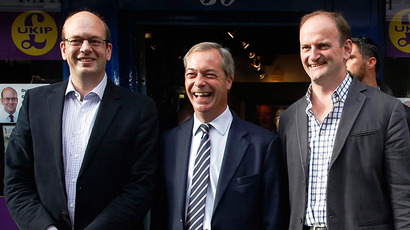 United Kingdom Independence Party (UKIP) leader Nigel Farage (2L) reacts with former Conservative MP and UKIP candidate Mark Reckless (L) and newly elected UKIP MP Douglas Carswell (3L) outside the party campaign office in Rochester southeast England October 11, 2014 (Reuters / Luke MacGregor)