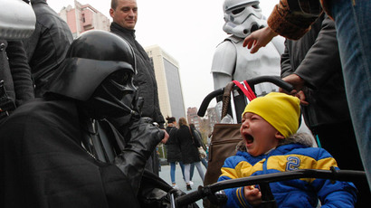 "A candidate, presenting himself in the character of ""Star Wars"" villain Darth Vader and representing the Internet Party of Ukraine which runs for parliament, gestures in front of a crying boy during a meeting with his supporters and voters in Kiev, October 22, 2014. (Reuters / Valentyn Ogirenko )"