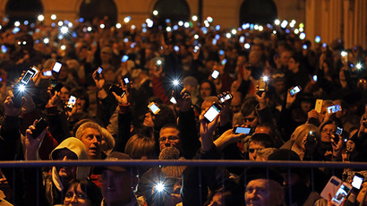 People hold up their mobile phones as they protest against new tax on Internet data transfers in centre of Budapest October 26, 2014. (Reuters/Laszlo Balogh)