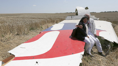 George and Angela Dyczynski sit on a piece of wreckage of the downed Malaysia Airlines Flight MH17, during their visit to the crash site near the village of Hrabove (Grabovo), in Donetsk region July 26, 2014. (Reuters/Sergei Karpukhin)