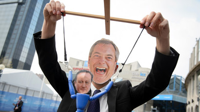 A man wearing a mask depicting  Nigel Farage dangles a puppet representing Conservative Party leader and Prime Minister, David Cameron. (AFP Photo / Leon Neal)