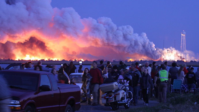 People who came to watch the launch walk away after an unmanned rocket owned by Orbital Sciences Corporation exploded (background) October 28, 2014. (AFP Photo/Steve Alexander)