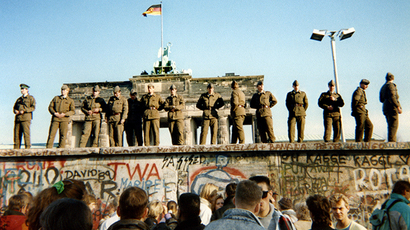 East German border guards stand on a section of the Berlin wall with the Brandenburg gate in the background on November 11, 1989 in Berlin. (AFP Photo / Gunther Kern)
