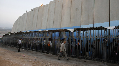 Palestinians wait to cross into Jerusalem next to Israel's controversial barrier at an Israeli checkpoint in the West Bank town of Bethlehem (Reuters/Ammar Awad)