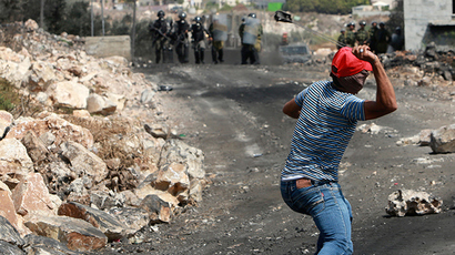 A Palestinian protester uses a sling to throw stones towards Israeli border policemen during clashes following a protest against the near-by Jewish settlement of Qadomem, in the West Bank village of Kofr Qadom near Nablus (Reuters / Abed Omar Qusini)
