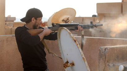 A member of the pro-government Libyan forces fires from the top of a building during a attack on districts held by Islamist militias on November 3, 2014 around the port of eastern Libya's restive city of Benghazi. (AFP Photo)