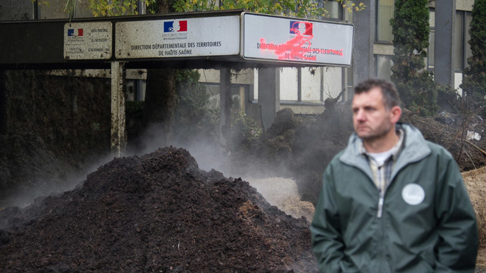A farmer passes by the main entrance of the DDT (Direction Departementale des territoires) with a manure stacked outside during a protest in Vesoul, France on November 5, 2014.(AFP Photo / Sebastien Bozon)