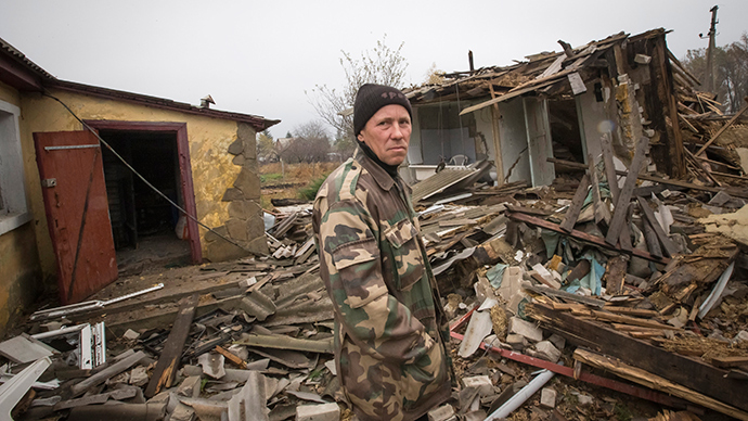 A man looks on next to his neighbor's house, which was destroyed by shelling in the village of Spartak, on the outskirts of Donetsk, eastern Ukraine (Reuters / Shamil Zhumatov)
