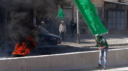 A Palestinian protester holds a Hamas flag during clashes with Israeli troops following a protest against what organizers say are recent visits by Jewish activists to al-Aqsa mosque, at Qalandia checkpoint near the West Bank city of Ramallah November 7, 2014 (Reuters / Ammar Awad)