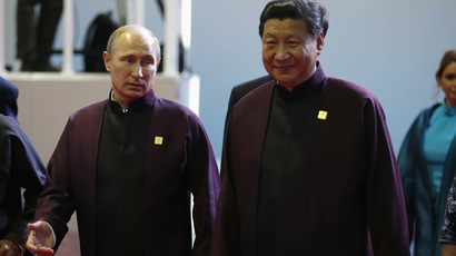 Russian President Vladimir Putin and Chinese President Xi Jinping talk as they depart the APEC Summit family photo, in Beijing November 10, 2014. (Reuters/Kevin Lamarque)