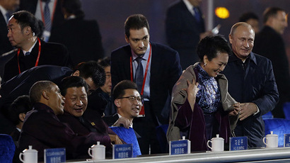 Russia's President Vladimir Putin (R) helps put a blanket on Peng Liyuan (2nd R), wife of China's President Xi Jinping at National Aquatics Center, or Water Cube, in Beijing, November 10, 2014. (Reuters/Stringer)