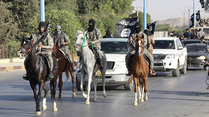 Militant Islamist fighters ride horses as they take part in a military parade along the streets of Syria's northern Raqqa province June 30, 2014. (Reuters/Stringer)