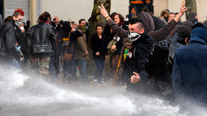 "A masked protestor taunts French riot police who use water canon at a demonstration against ""police brutality"" in Nantes, western France, November 22, 2014 (Reuters / Stephane Mahe)"