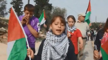 Tamimi and other young protesters march through their home village in the West Bank carrying Palestinian flags.(A screenshot from a video by YouTube user Bilal Tamimi)
