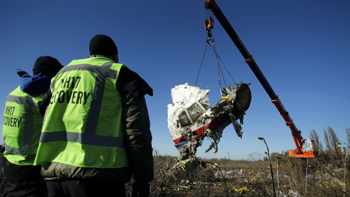nvestigators watch as a piece of wreckage from the Malaysia Airlines flight MH17 is transported at the site of the plane crash near the village of Hrabove (Grabovo) in Donetsk region, eastern Ukraine November 20, 2014. (Reuters/Antonio Bronic)