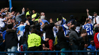 An Atletico Madrid fan (R) gets the acknowledgement of Deportivo Coruna's supporters after throwing them his team's scarf during their Spanish first division soccer match at Vicente Calderon stadium in Madrid, November 30, 2014. (Reuters / Susana Vera)
