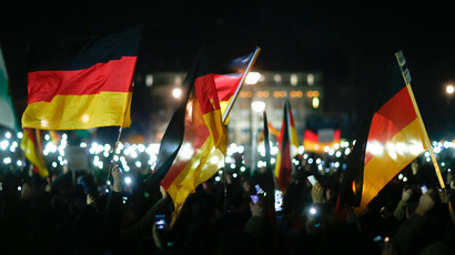 "Participants hold up their mobile phones and wave German national flags during a demonstration called by anti-immigration group PEGIDA, a German abbreviation for ""Patriotic Europeans against the Islamization of the West"", in Dresden December 8, 2014.(Reuters / Hannibal Hanschke)"