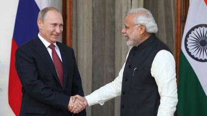 Russian President Vladimir Putin (L) shakes hands with Indian Prime Minister Narendra Modi at Hyderabad House in New Delhi on December 11, 2014. (AFP Photo/Findlay Kember)
