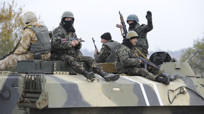 Ukrainian army soldiers sitting atop an armoured vehicle maneuver on the coastline near the eastern Ukrainian city of Mariupol on October 21, 2014. (AFP Photo)