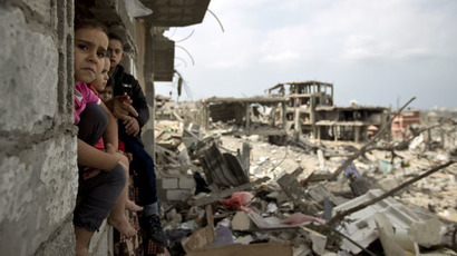 Palestinian children sit on the window of a partially destroyed building in al-Tufah, east of Gaza City on October 11, 2014 (AFP Photo/Mahmud Hamas)